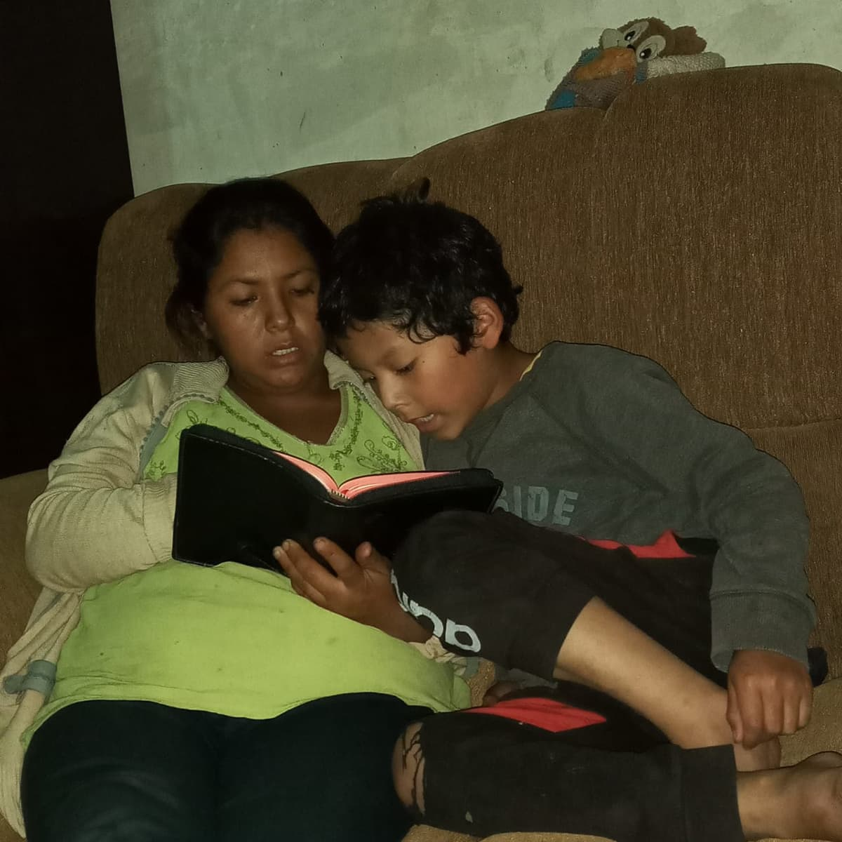 A Bolibian woman sits on a bed with her son and reads the Bible.