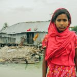 Aduri, wearing a red dress and headscarf, stands in front of her collapsed bamboo home.