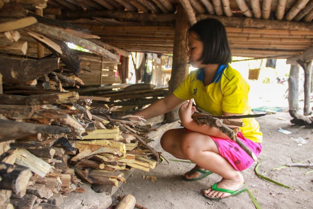 Young girl wearing a yellow shirt and pink shorts collects firewood below a bamboo home