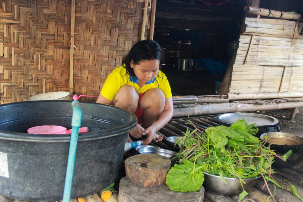 Young girl in a yellow shirt crouches to wash vegetables outside.