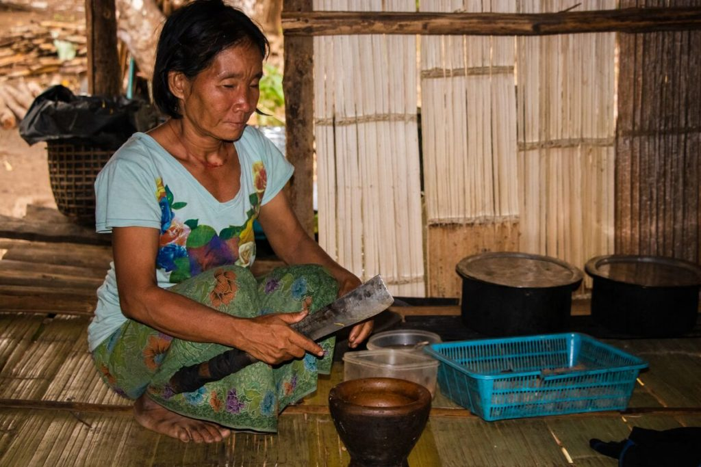 A woman wearing a blue shirt crouches in her home with a knife cutting food to eat. She's in a bamboo home.