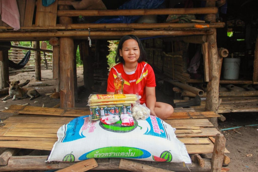 Young girl in red shirt smiles with a big bag of rice and some other food in front of her.