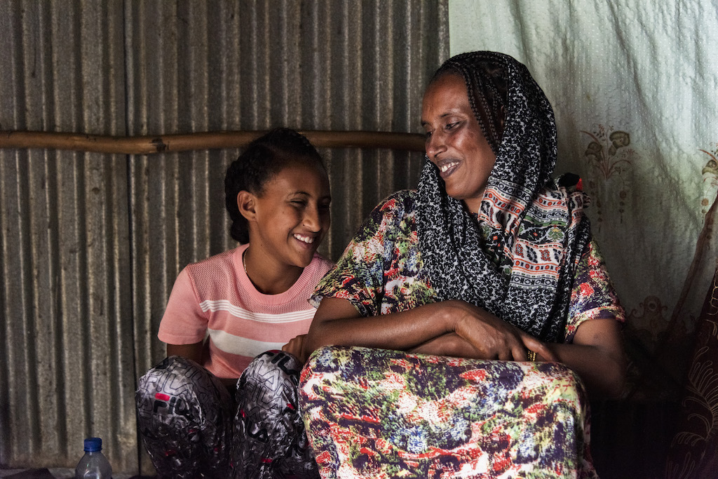 Meseret and Saron sit, smiling at each other.