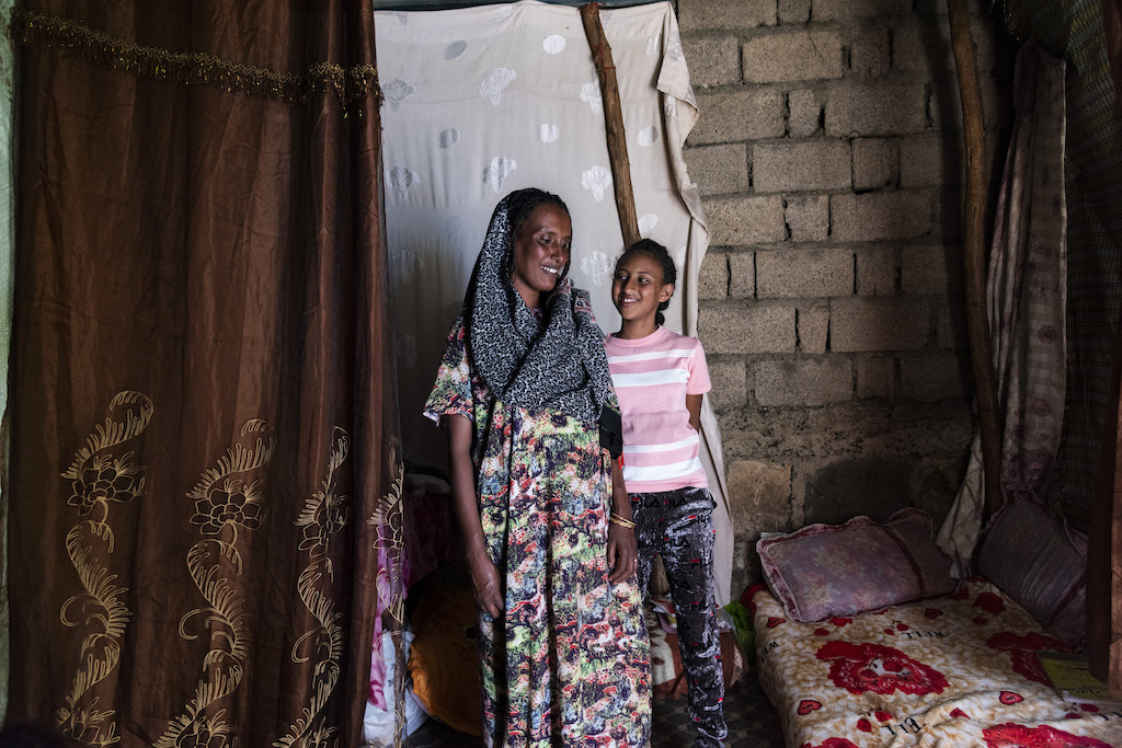 Meseret and Saron stand together in their home.