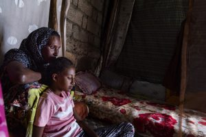 Meseret and Saron sit beside their bed.