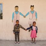 Boy and girl hold hands in font of a mural of a boy and a girl holding hands