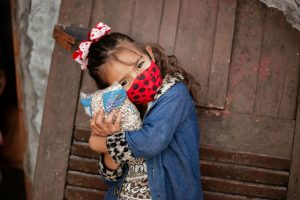 Little girl wears a red mask and hugs a bag of beans
