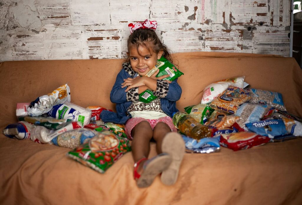Little girl on her couch surrounded in packaged foods, smiling