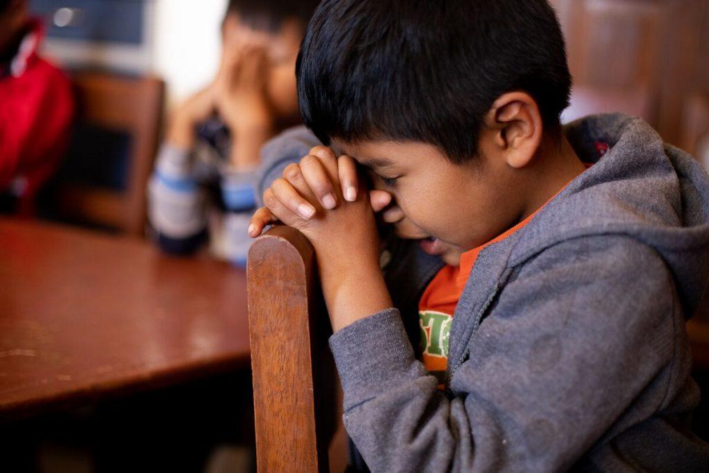 Little boy in a hoodie in praying