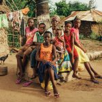 A large family sits in their yard in Kenya.