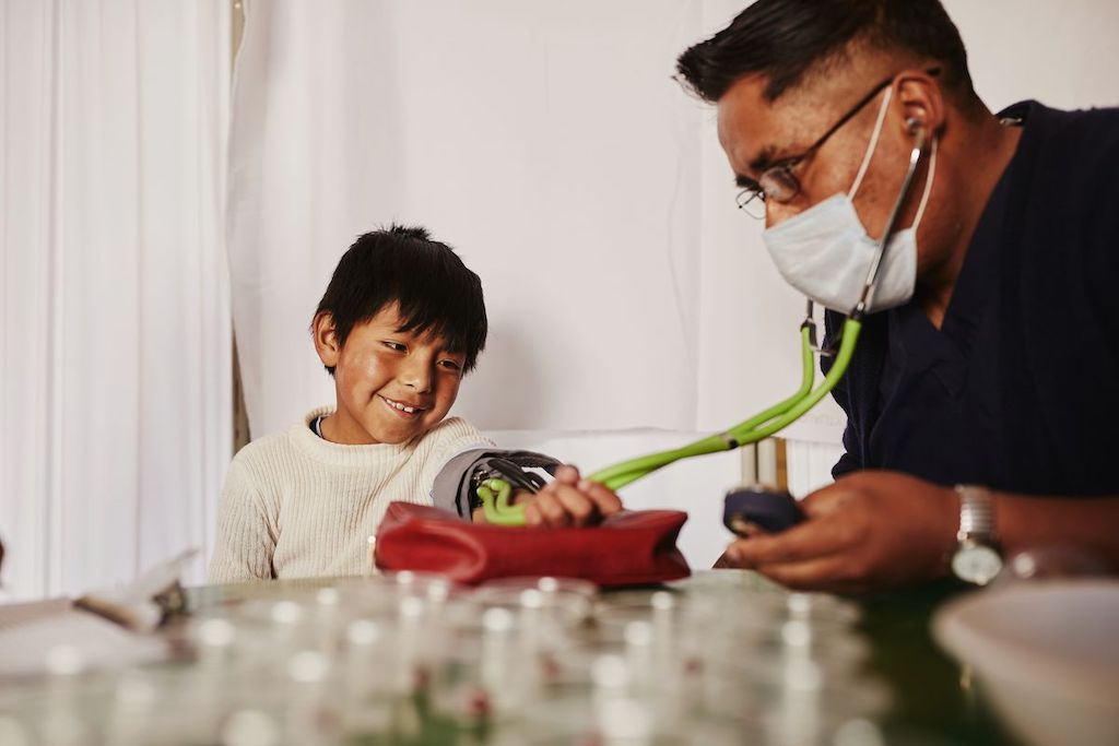 A doctor examines a young boy in Bolivia.