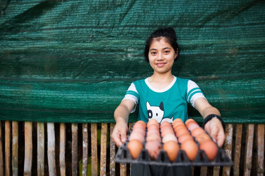 A Thai girl holds a tray of eggs.