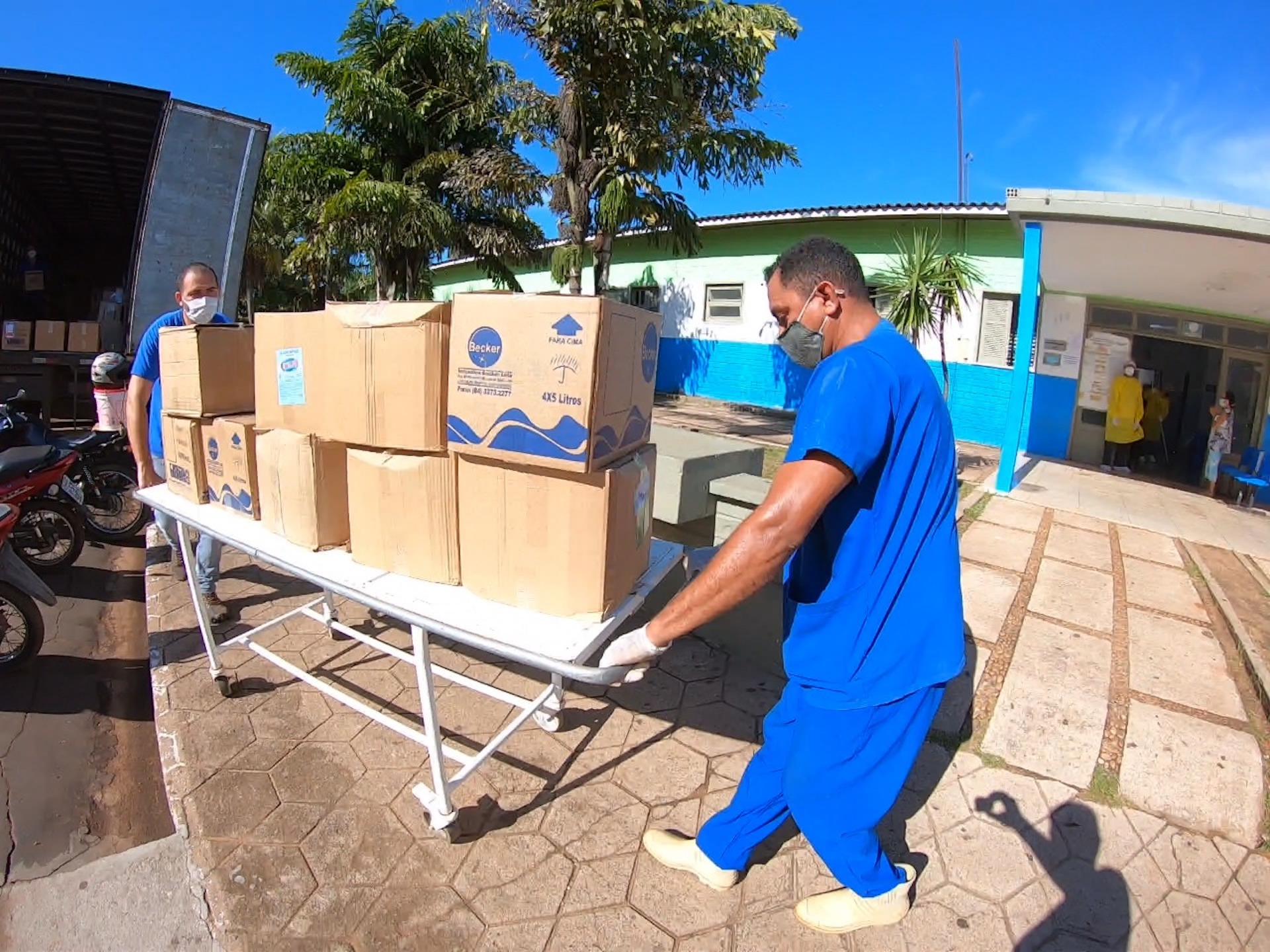 Hospital staff wearing blue scrubs unload several boxes of supplies into the hospital.