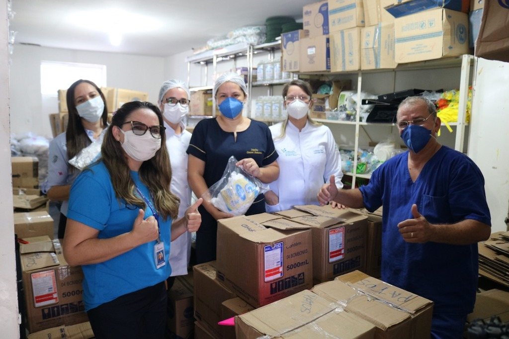 A group, all wearing masks, stand in a storage room amongst boxes of donated supplies.