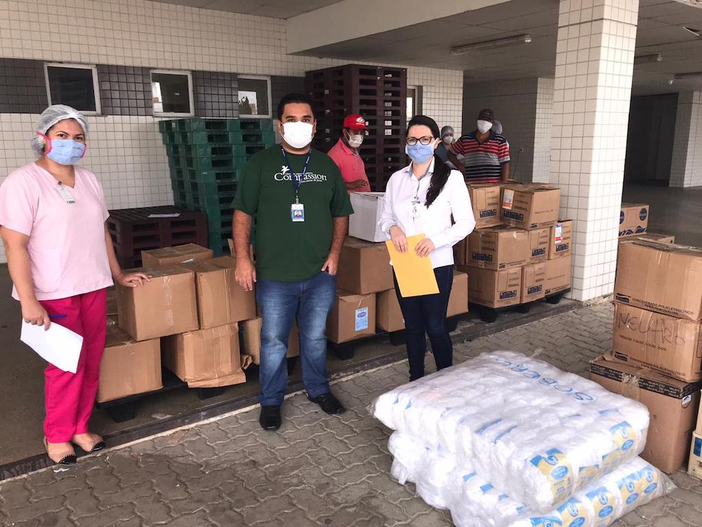 Compassion staff and hospital staff stand together outside the hospital with boxes of donated supplies. All are wearing masks.