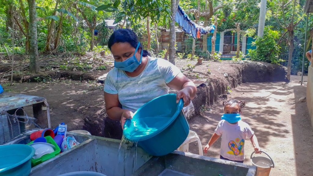 Yesenia fills up her sink with water from the water tank truck. Her daughter, Raquelita, follows behind with a bucket of water.