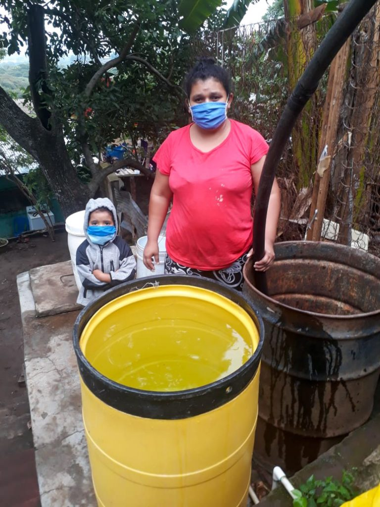 Petrona fills up her barrels with water from the water tank truck that Compassion provided.