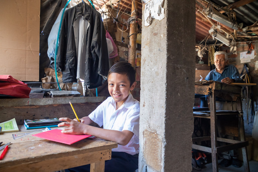 Eleazar sits at a table in his home doing schoolwork. His dad sits at a table in the background.