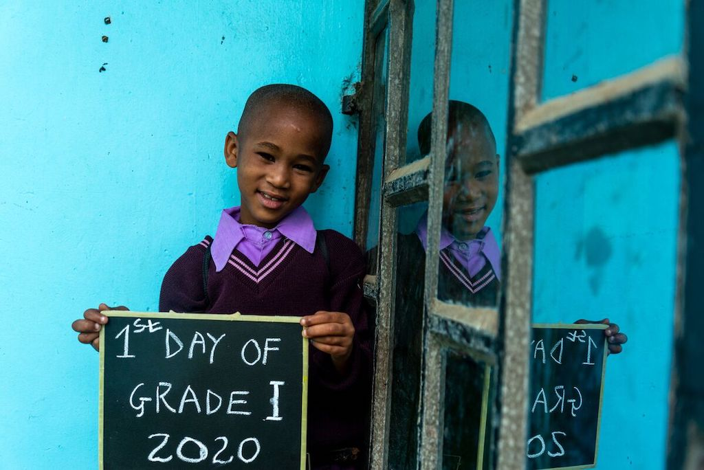 "Hamisi stands against a blue wall holding a chalkboard that says ""1st day of grade 1, 2020""."