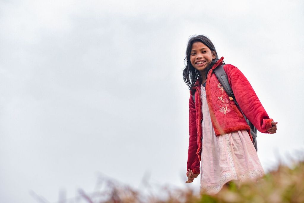 Anushka stands on a hill wearing a pink dress, red coat and her school backpack.
