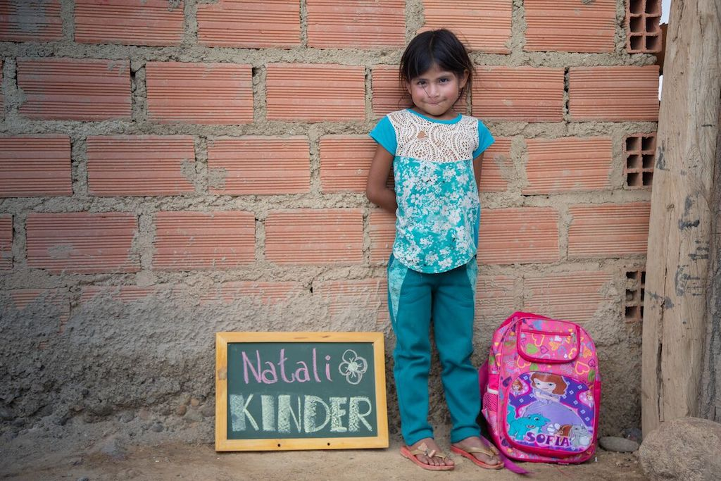 "Natali stands against a brick wall with her pink backpack next to her and a chalkboard that says ""Natali KINDER"" on her other side."