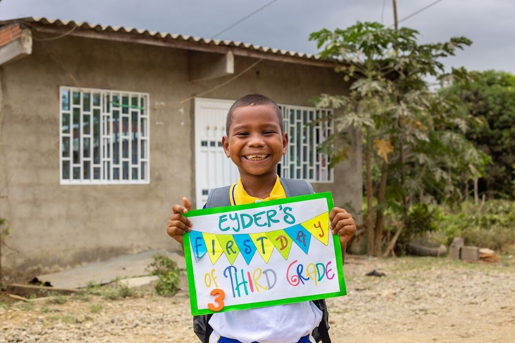 "Eyder stands in front of his home holding a card that says ""Eyder's first day of third grade""."