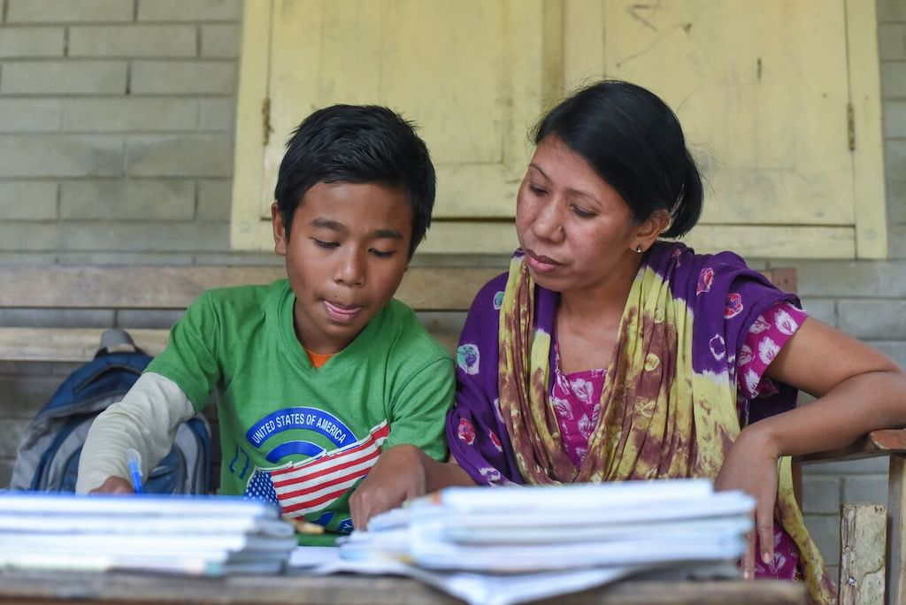 Woochang and his mother sit at a table doing schoolwork.