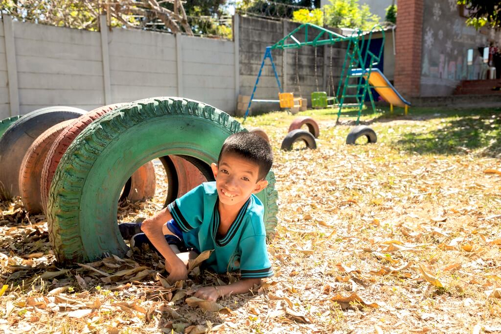 Levi plays on the playground, crawling through colourful tires