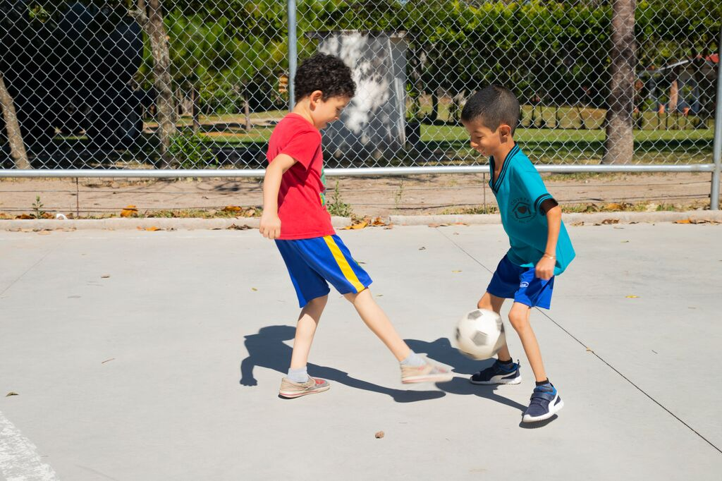 Levi plays soccer on a basketball court with a friend.