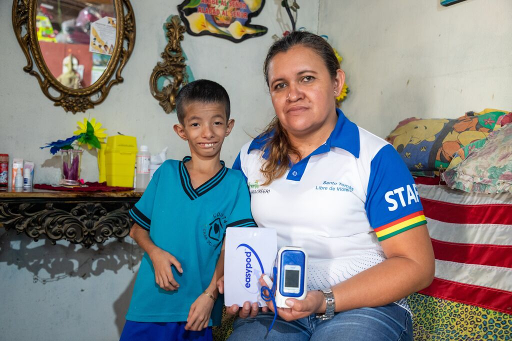 Levi and his mom pose with the medical device he uses for administering his growth hormones