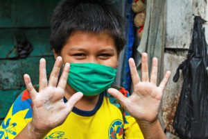 Ten-year-old Carmelo wears a green mask and yellow shirt and holds up both his hands to show they are freshly washed.