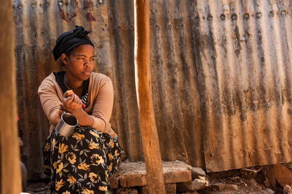 Abiyot is pictured outside her home holding a cup in her hand. She looks upset.