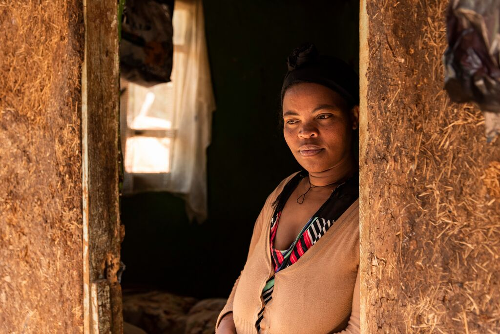 Abiyot stands in her doorway with a hopeful look on her face.
