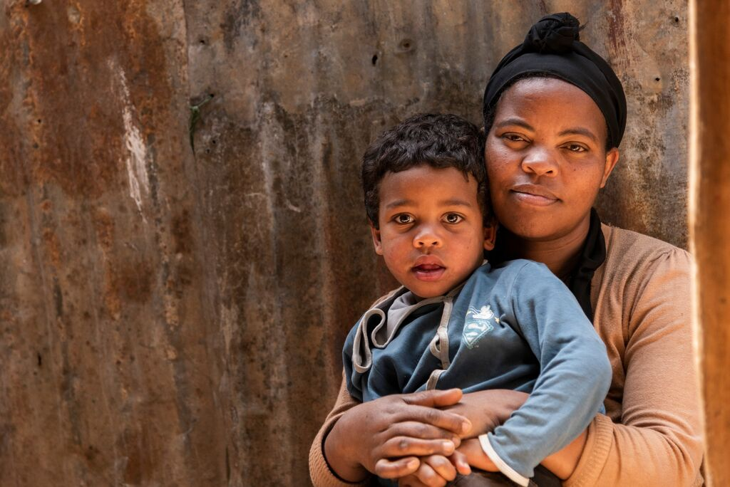 Abiyot and her young son pose together in front of their home