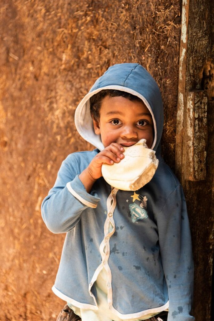 Abiyot's young son, Habtemariam, wears a blue hoodie and chews on some bread.