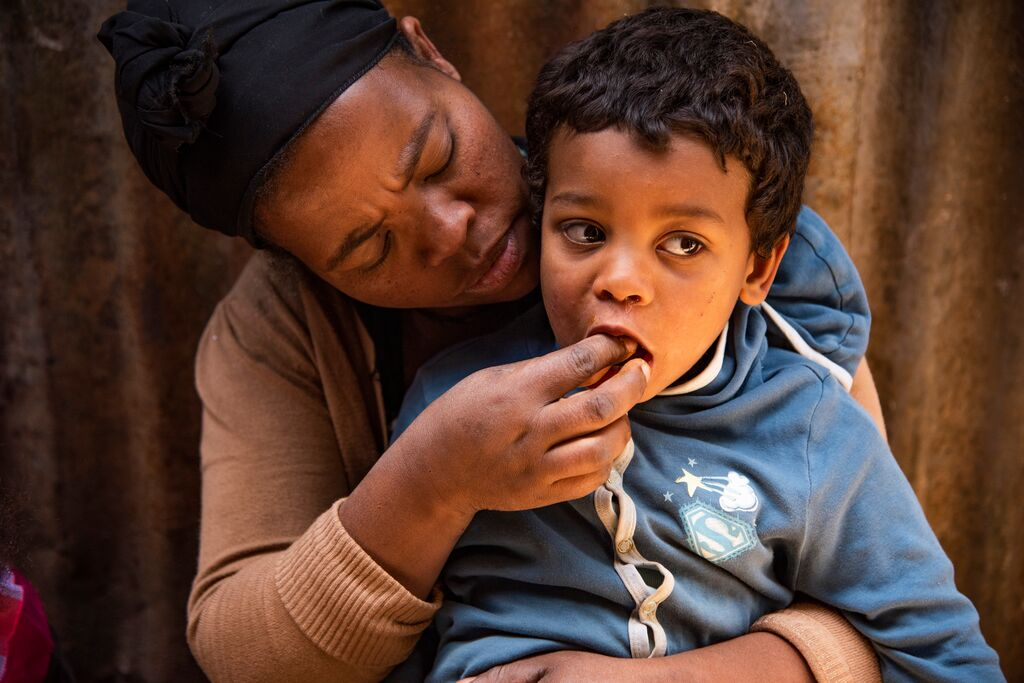 Abiyot feeds her young son some bread into. his mouth.