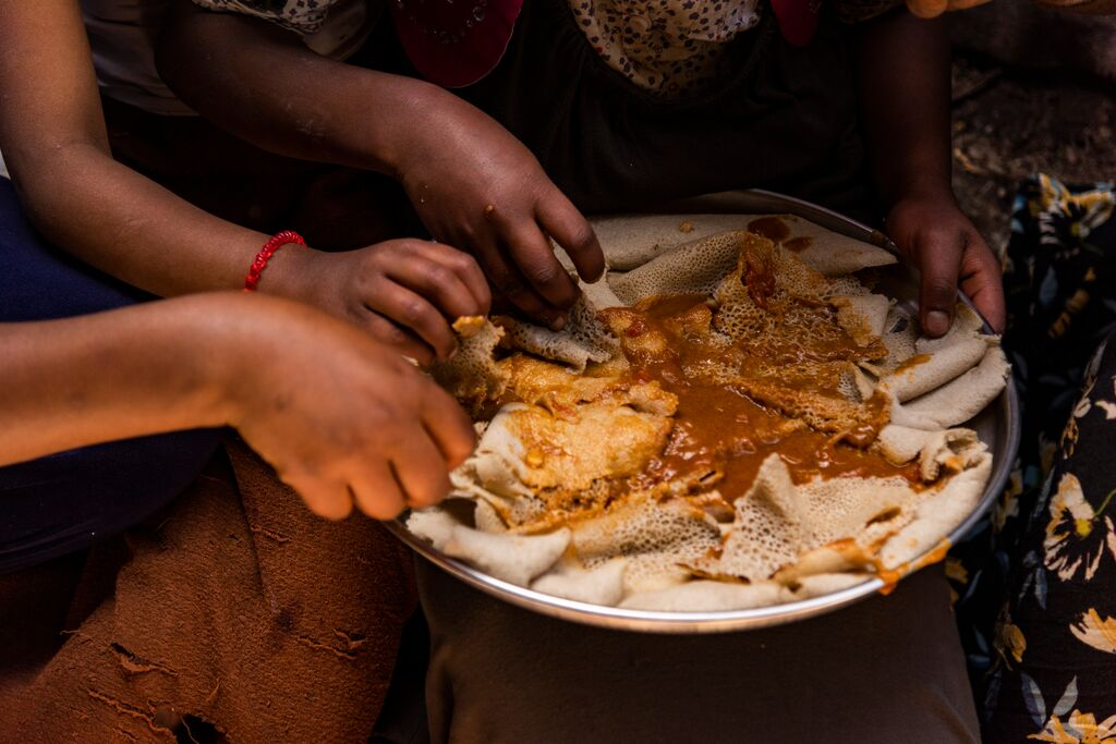 A close up picture of the family eating a plate of injera and Shiro stew, a traditional Ethiopian dish.