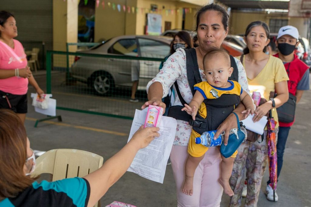 A mother receives multi-vitamins and a paper with health instructions in the Philippines