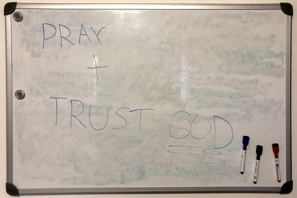 """A whiteboard with the words """"Pray and trust God"""" written on it."""