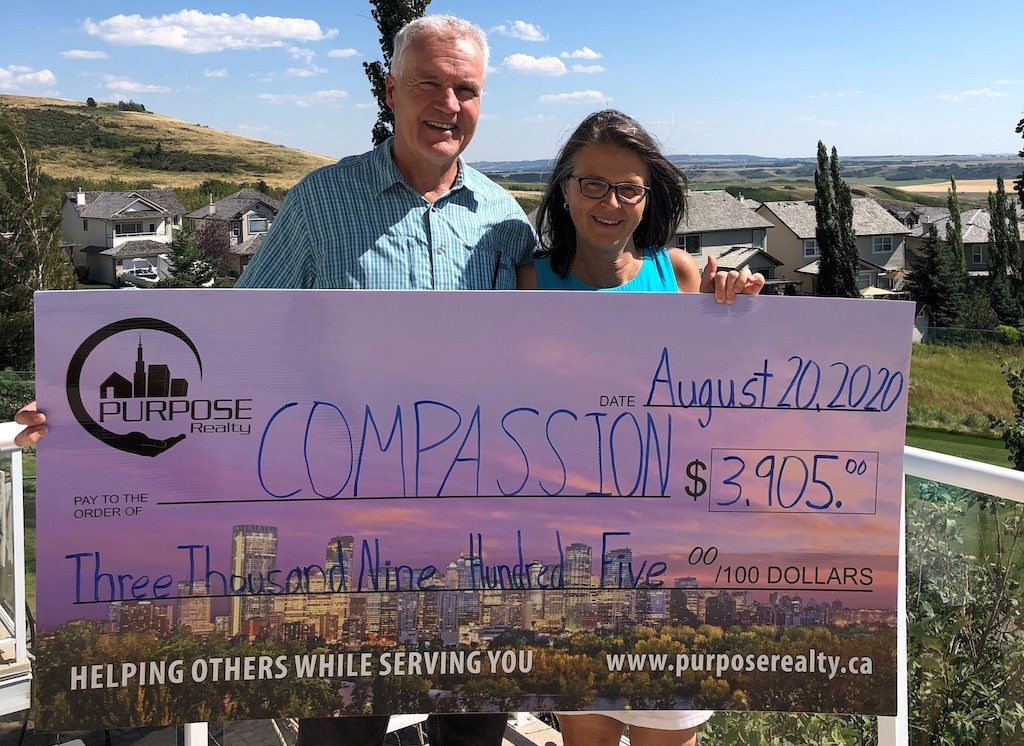 """A couple holds a large cardboard cheque made out to """"Compassion""""."""