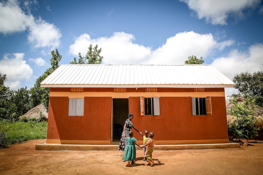 Annet and her triplets after they received their new home over two years ago.