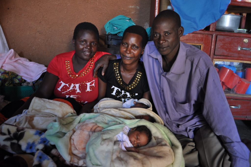 Annet is seen holding her triplets while sitting in between a man in a blue shirt and a woman in a red shirt.