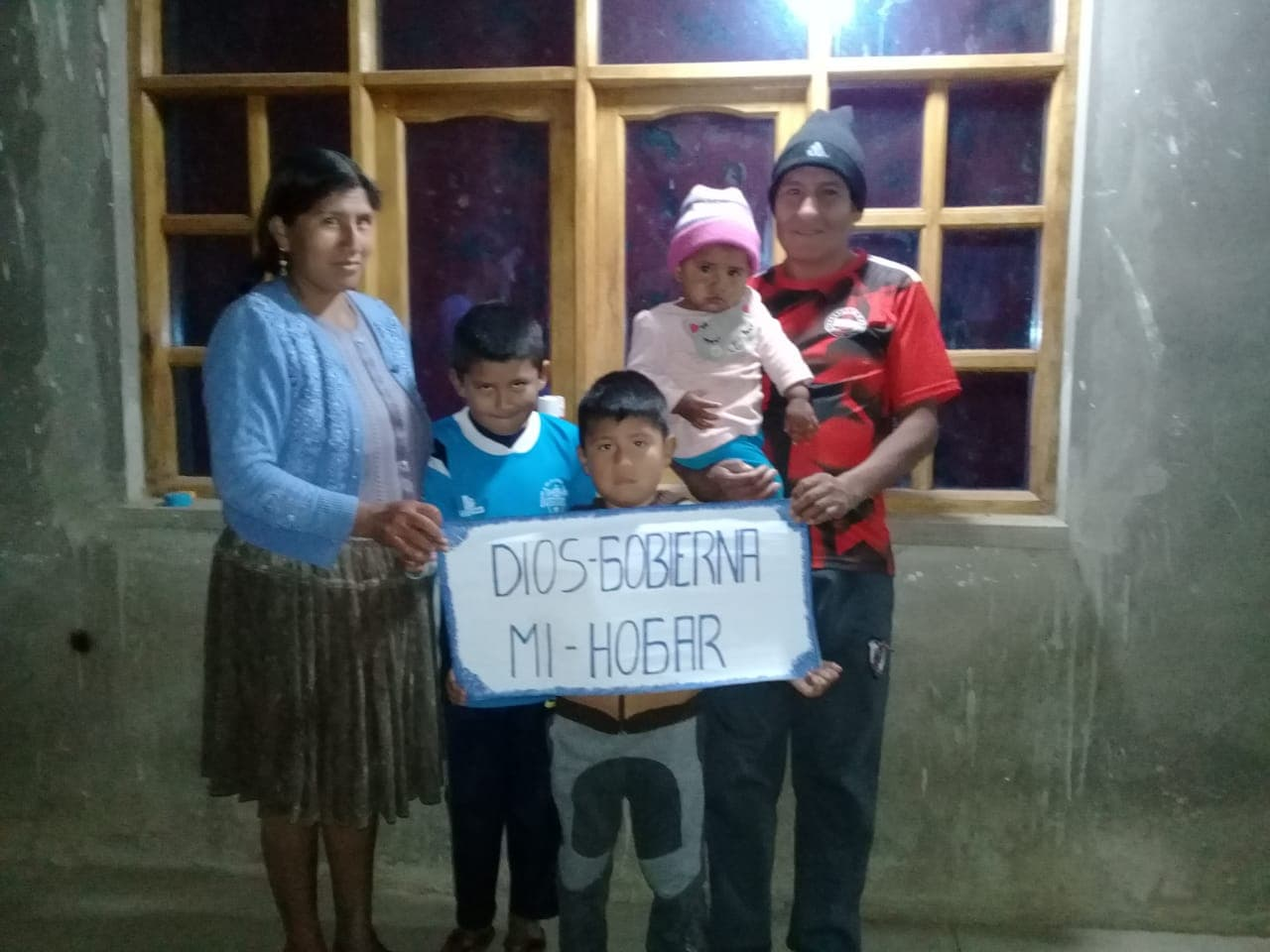 A family stands together holding a sign.