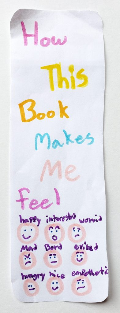 """A hand-drawn bookmark with the words """"How this book makes me feel"""" and emojis drawn on it."""