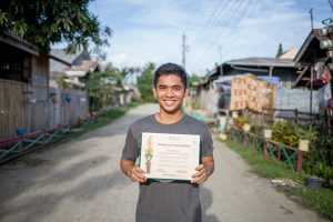 Stephen stands in the street, holding a certificate.