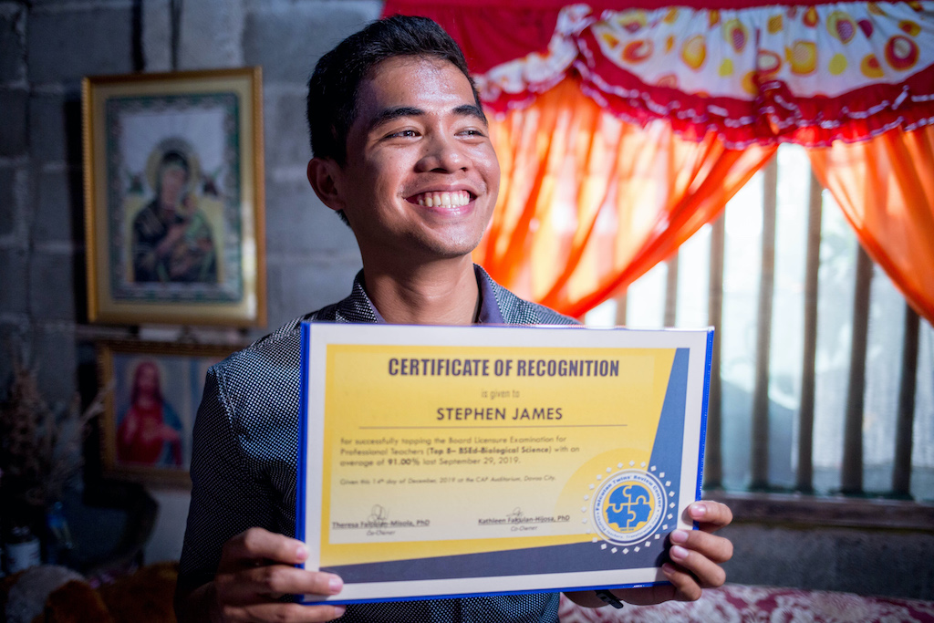 Stephen sits in his home, smiling and holding up a certificate of recognition.