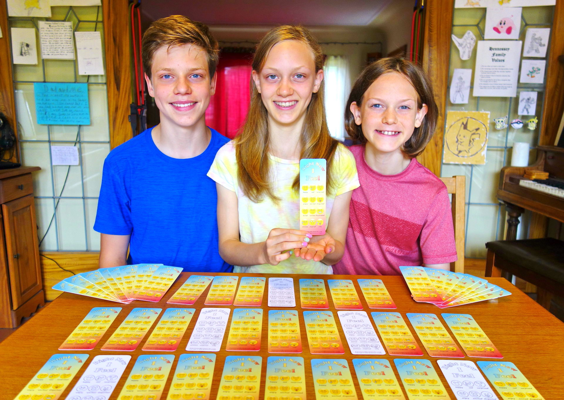 3 children where middle 1 is holding a bookmark.