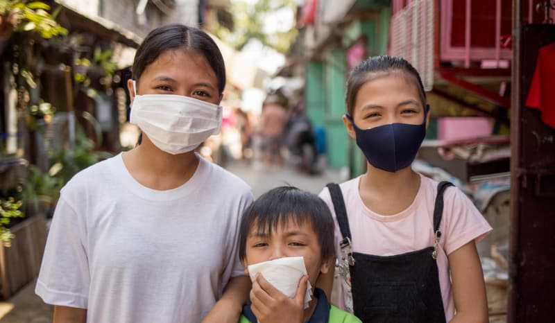 Three children standing together wearing masks.