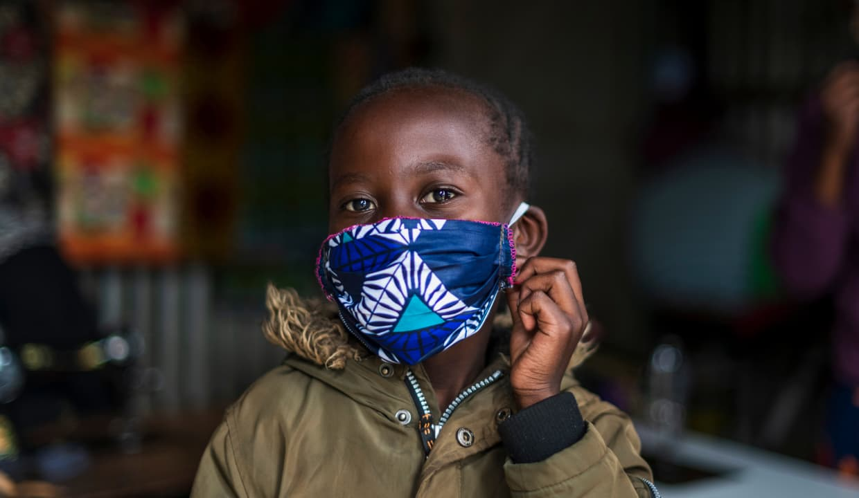 Young boy holding onto the side of his mask.