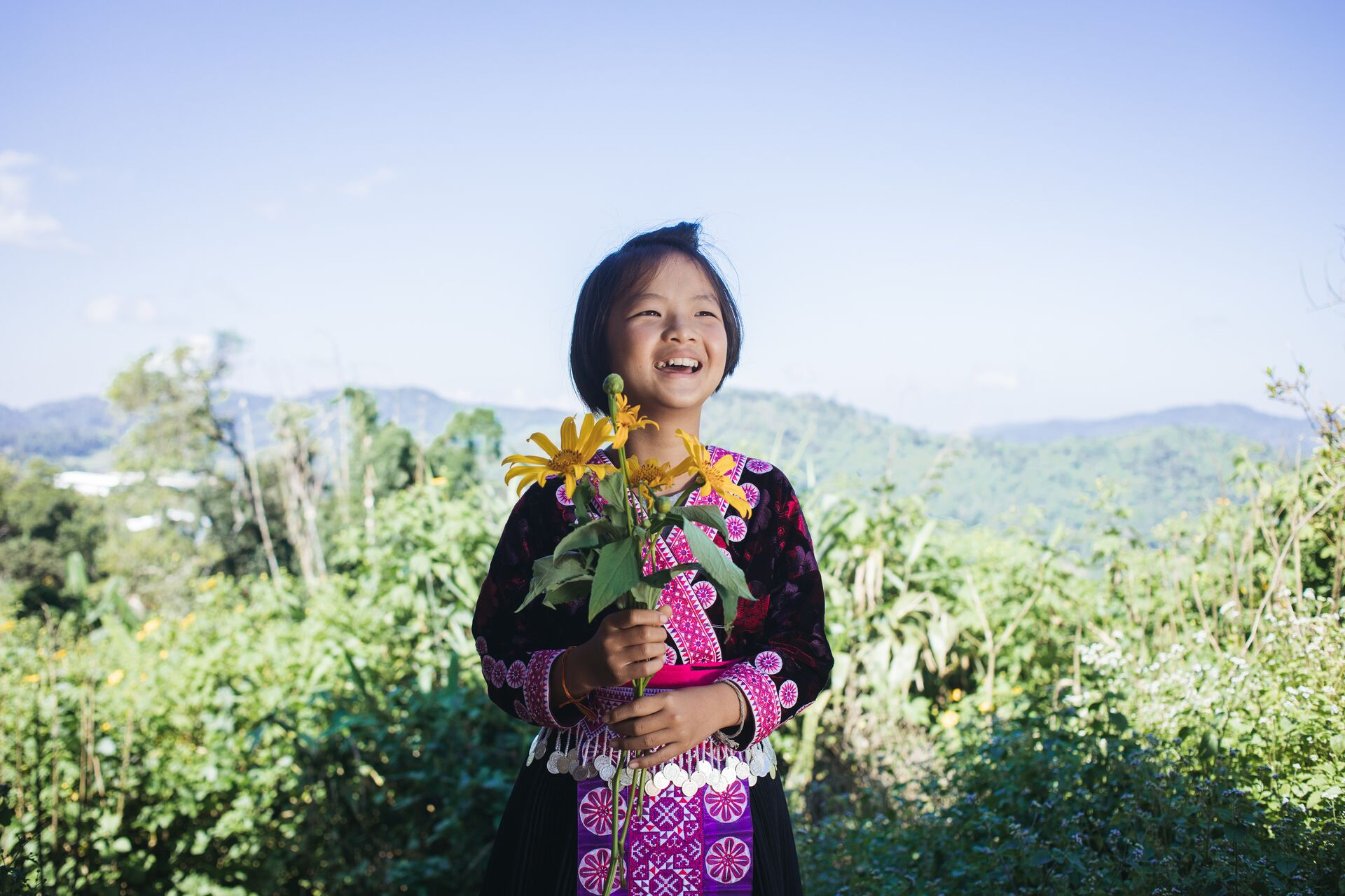 Girl smiles in a field and holds a bouquet of flowers.